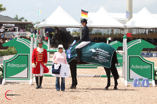 Sloane Coles and WEC l'Ami Noir in their winning presentation with ringmaster Gustavo Murica and Laura Fetterman of Champion Equine Insurance